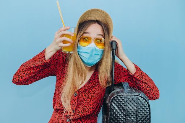 Ragazza in abito, cappello e occhiali da sole con mascherina medica sul viso e cocktail nelle sue mani.