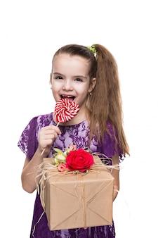 Ragazza in abito di pizzo viola che tiene una scatola con un regalo decorato con fiori.