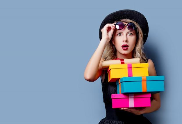 Ragazza in abito nero e cappello con scatole regalo