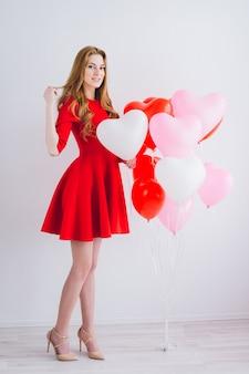 Ragazza in abito rosso con palloncini a forma di cuore