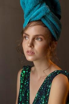 Ragazza in abito verde-blu lucido e asciugamano sulla testa