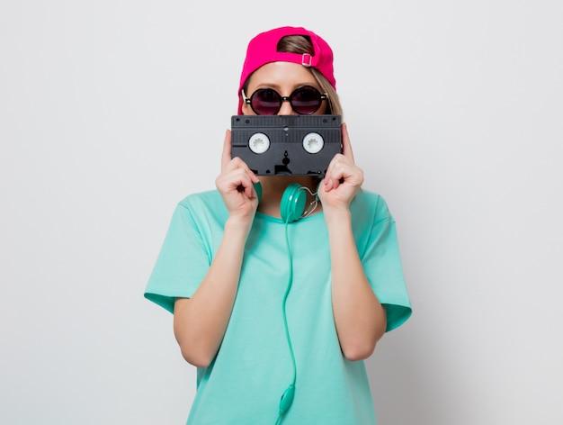 Ragazza in berretto rosa e maglietta blu con cassetta vhs
