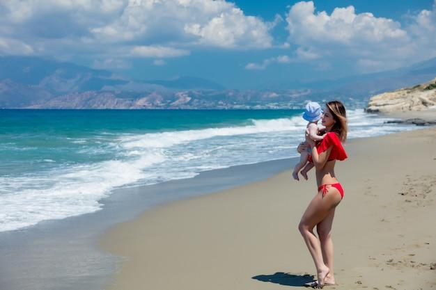 Ragazza in bikini rosso e bambino sulla spiaggia di tympaki