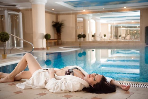 Ragazza in bikini vicino alla piscina nel salone spa day resort