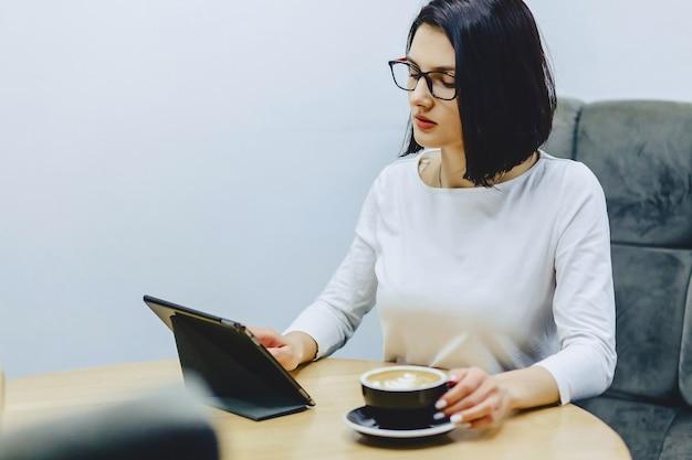 Ragazza in caffè beve caffè e lavora su tablet
