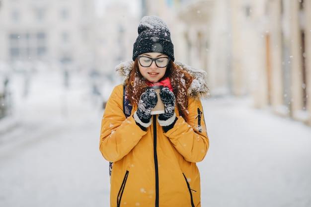 Ragazza in caffè bevente del cappotto giallo all'aperto. la donna sola si trova su una strada innevata d'inverno in città