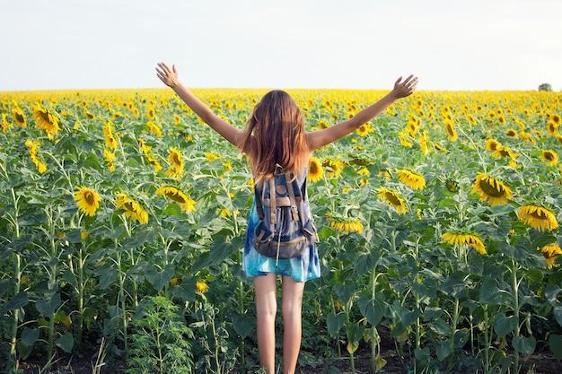 Ragazza in campo di girasole, una ragazza emotiva, una ragazza entra in un campo di girasoli, vista da dietro; copia spazio