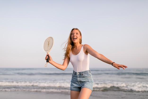 Ragazza in canottiera sportiva e shorts giocando a tennis in riva al mare