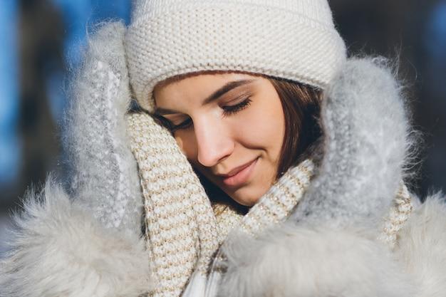Ragazza in cappello e guanti che sorridono in inverno