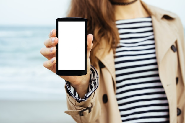 Ragazza in cappotto beige e t-shirt a righe mostra un telefono schermo vuoto sullo sfondo del mare
