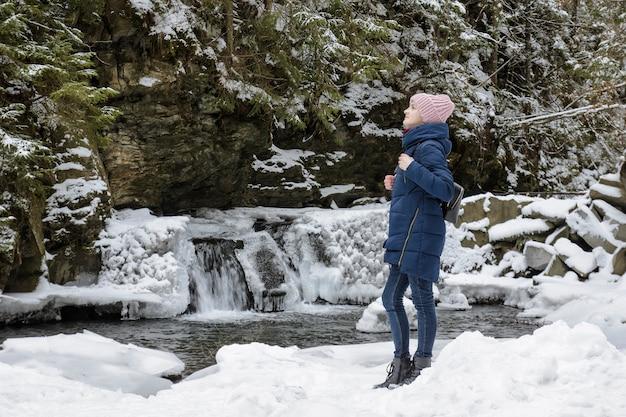 Ragazza in cappotto blu che sta su una cascata ghiacciata e rocce in una foresta di conifere innevata