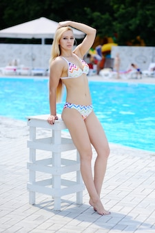 Ragazza in costume da bagno bianco sullo sfondo della piscina
