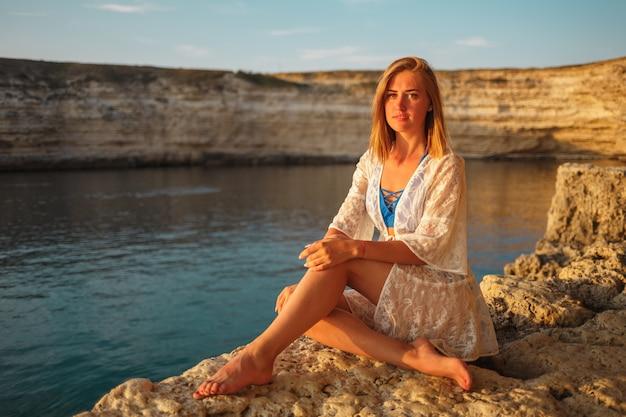 Ragazza in costume da bagno blu su una spiaggia rocciosa