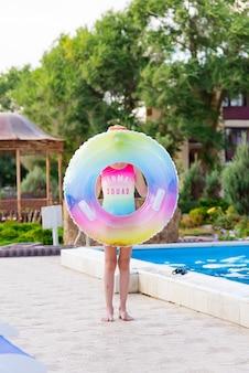 Ragazza in costume da bagno con anello gonfiabile