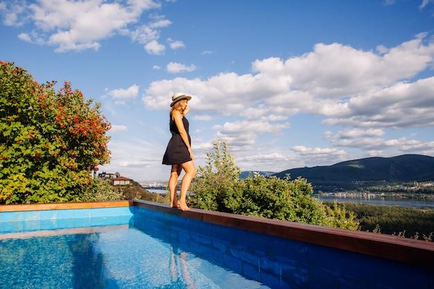 Ragazza in costume da bagno sul bordo della piscina