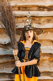Ragazza in costume della strega che fa fronte con il manico di scopa