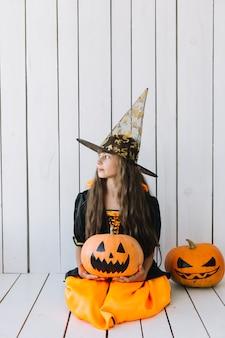 Ragazza in costume di halloween che si siede e che tiene zucca in studio