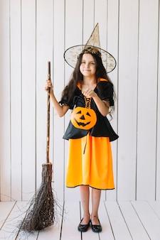 Ragazza in costume di halloween con cesto di zucca e scopa in piedi in studio