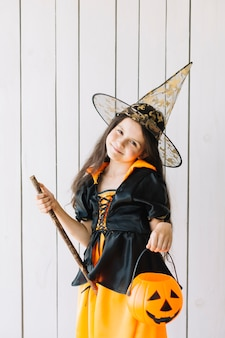 Ragazza in costume di halloween con cesto di zucca in posa in studio
