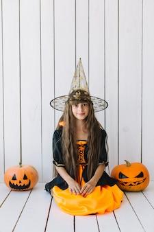 Ragazza in costume di halloween con zucche sui lati seduto in studio