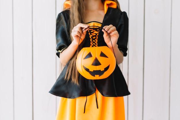 Ragazza in costume di halloween tenendo il cesto di zucca