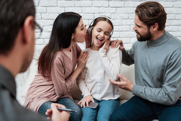 Ragazza in cuffie ignorando i genitori in terapia