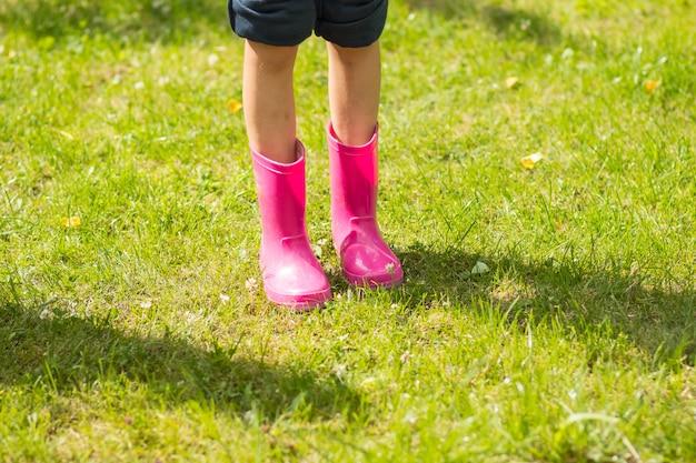 Ragazza in divertenti stivali di gomma in piedi nel giardino dopo la pioggia.