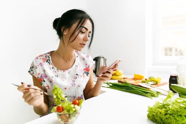 Ragazza in forma controlla il suo telefono e mangia insalata in cucina