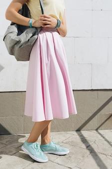 Ragazza in gonna rosa, camicia gialla e con uno zaino in piedi contro un muro bianco