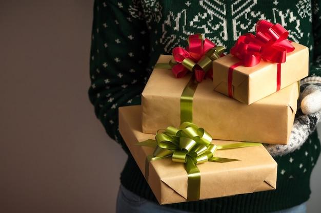 Ragazza in guanti e un maglione con un ornamento invernale detiene i regali di natale