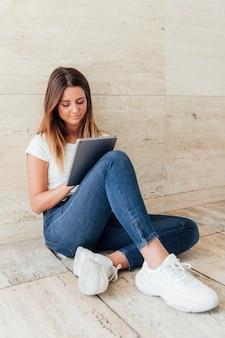 Ragazza in jeans con un tablet
