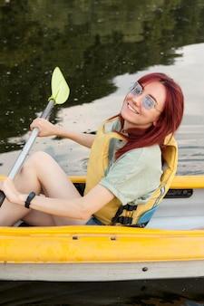 Ragazza in kayak sorridente e tenendo la pagaia