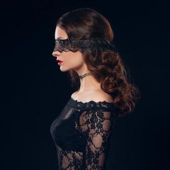 Ragazza in lingerie maschera nera su sfondo nero