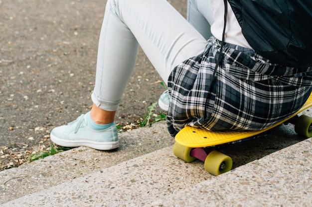 Ragazza in maglietta bianca e jeans che si siedono sullo skateboard di plastica giallo