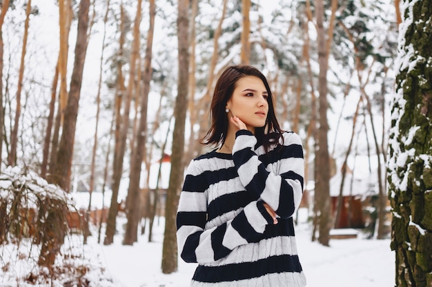 Ragazza in maglione bianco e nero al freddo nella foresta sotto i pini