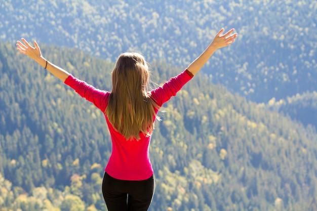 Ragazza in maglione rosso in piedi su grandi rocce nelle montagne sollevando le mani