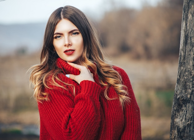 Ragazza in maglione rosso nella foresta
