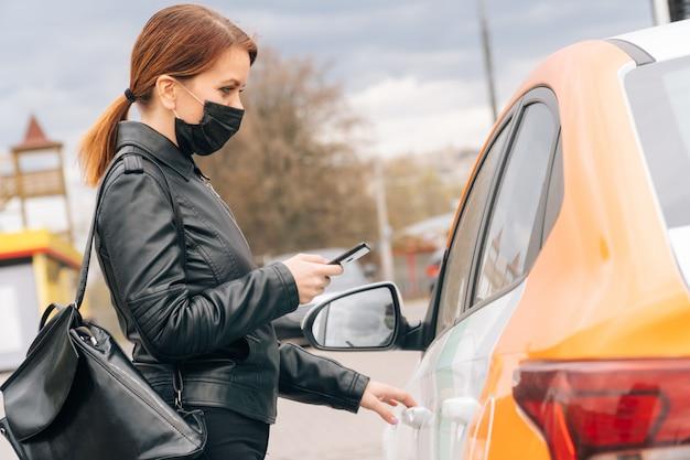 Ragazza in maschera medica noleggia auto per un viaggio in ospedale. il concetto di pagamento non cash sull'app mobile