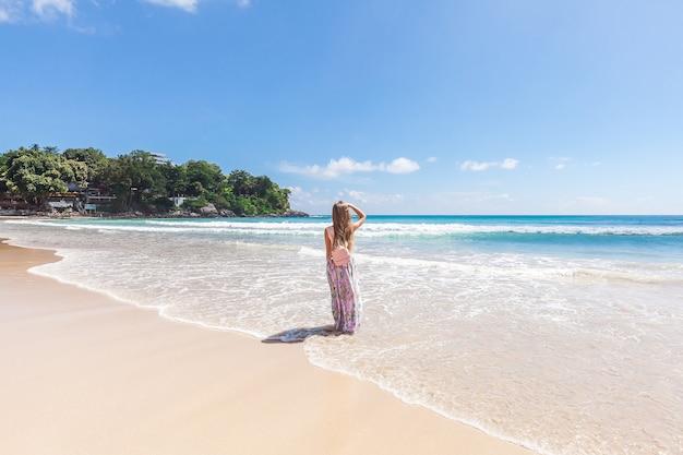 Ragazza in maxi gonna rosa floreale che cammina sulla riva del mare