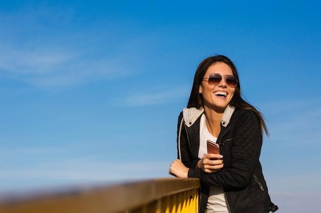 Ragazza in occhiali da sole sorridente al di fuori