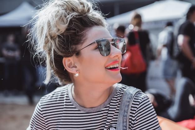 Ragazza in occhiali da sole vintage con ritratto di tatuaggi close-up per la strada durante un picnic con gli amici. ragazza fredda