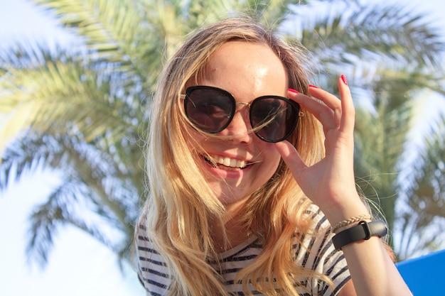 Ragazza in occhiali e sorrisi braccialetto di fitness, in estate su uno sfondo di palme.