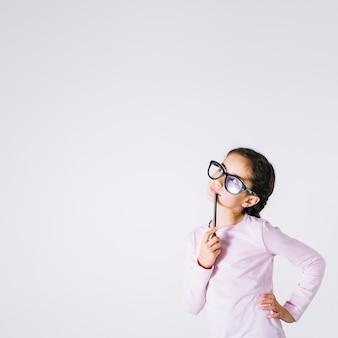 Ragazza in occhiali pensando e alzando lo sguardo