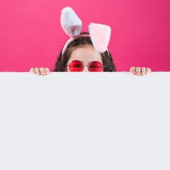 Ragazza in orecchie da coniglio e occhiali da sole che si nascondono dietro il tavolo