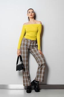 Ragazza in pantaloni a quadri e pullover giallo con piccola borsetta in posa vicino al muro bianco