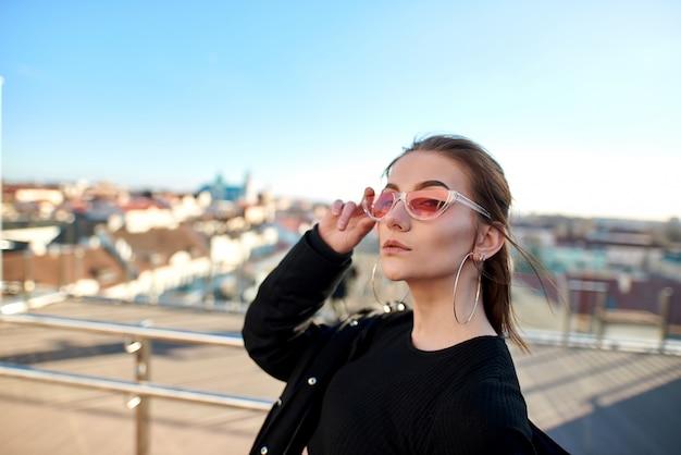 Ragazza in piedi al recinto di vetro e vetro è vista la città, in occhiali da sole rosa.