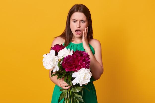 Ragazza in piedi con bouquet di peonie bordeaux e bianche tra le mani, vestita di prendisole verde, in posa con la bocca aperta, ha stupito l'espressione facciale, isolata sul giallo.
