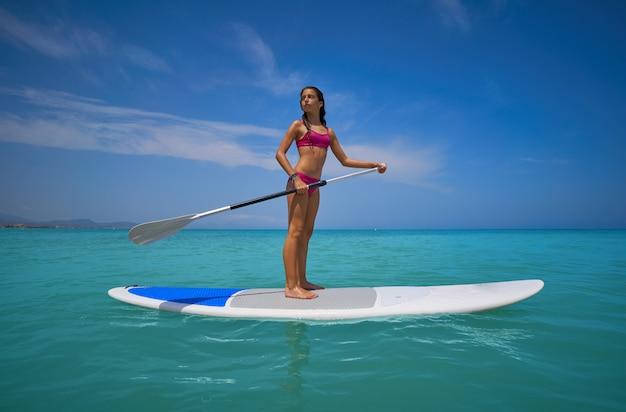 Ragazza in piedi sulla tavola da surf paddle sup