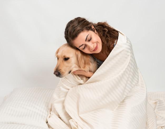 Ragazza in pigiama con un cane avvolto in una coperta bianca a casa