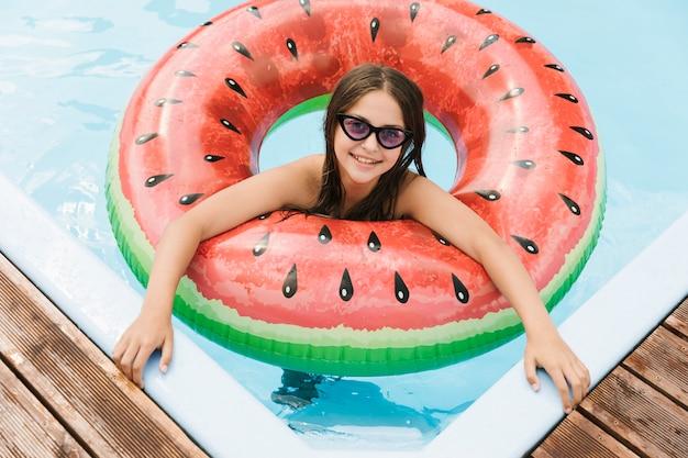 Ragazza in piscina con galleggiante di anguria